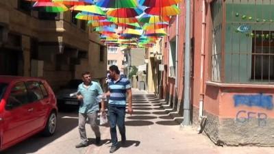 Turistlerin ilgisini çekmek için sokağı şemsiyelerle süsledi